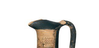 Πήλινη αττική τριφυλλόστομη οινοχόη. Στον ώμο φέρει εγχάρακτη μια από τις πρωϊμότερες γνωστές ελληνικές επιγραφές. Από την Αθήνα (Δίπυλο). 750-725 π.Χ. (© TAΠΑ/Εθνικό Αρχαιολογικό Μουσείο)