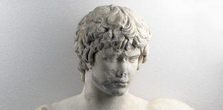 Γυμνή προτομή με κεφαλή του Αντίνοου. Βρέθηκε στην Πάτρα το 1856. Χρονολογείται λίγο μετά το 130 μ.Χ. Αρ. ευρ. Γ 418.