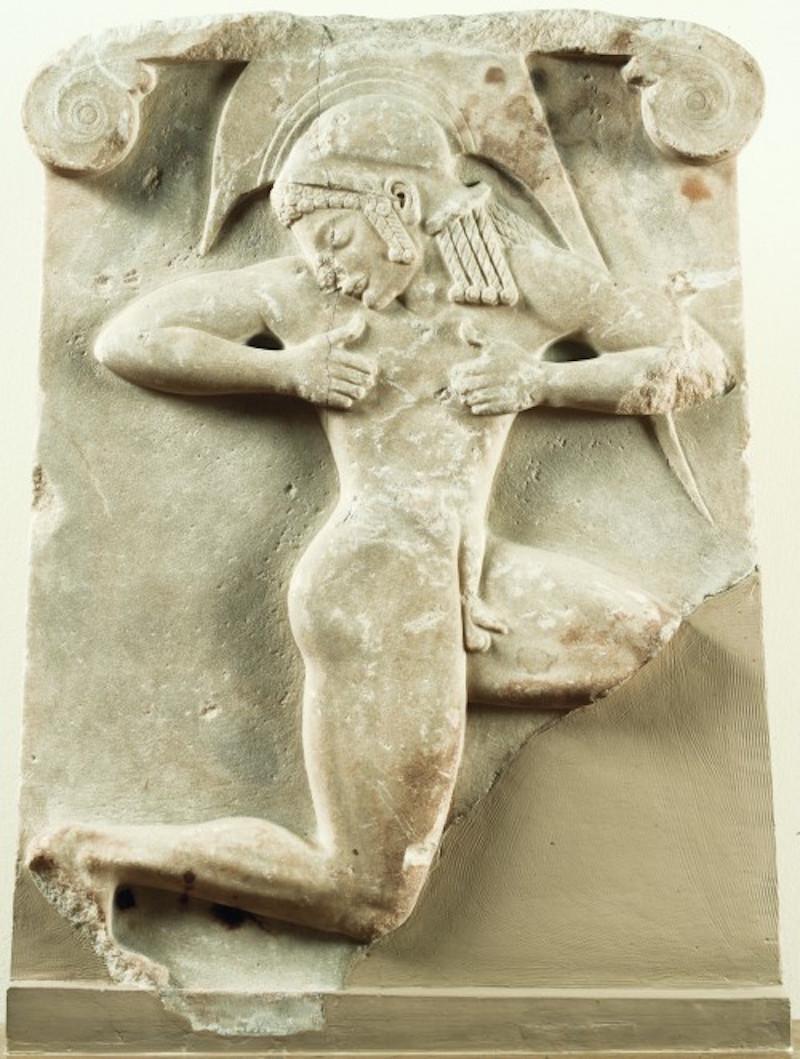 Επιτύμβιο ανάγλυφο «οπλιτοδρόμου». Βρέθηκε στην Αθήνα, ΝΔ του Θησείου. Γύρω στο 510 π.Χ. Γυμνός οπλίτης με αττικό κράνος παριστάνεται κινούμενος στο συμβατικό σχήμα του δρομέως. Η μορφή έχει ερμηνευθεί και ως χορευτής ενός πολεμικού χορού, του πυρριχίου. (© Εθνικό Αρχαιολογικό Μουσείο/TAΠΑ).
