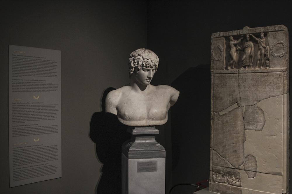 Εικονιστική προτομή του Αντίνοου, από την Πάτρα (130-138 μ.Χ.). Δίπλα της στήλη με κατάλογο των αξιωματούχων του Γυμνασίου και των εφήβων κατά φυλές. Από την Αθήνα. Γύρω στο 212/213 μ.Χ.